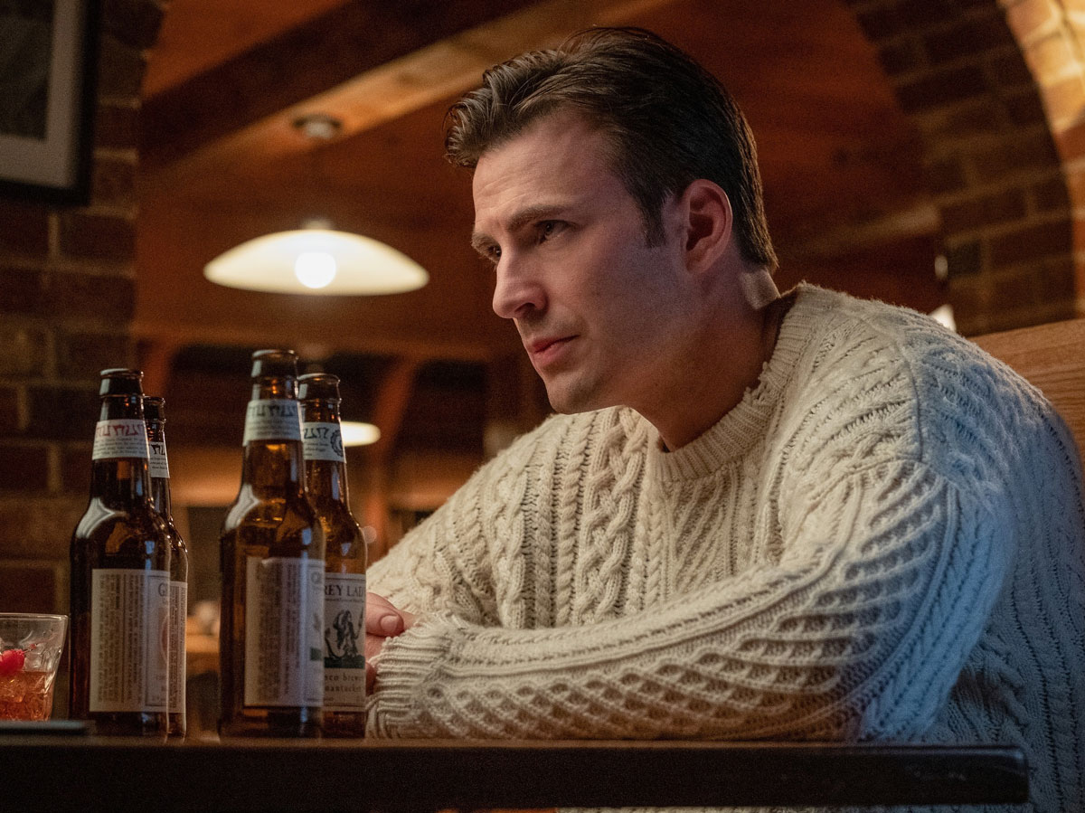 Chris Evans leans on a table in white cable knit sweater with four empty beer bottles in front of him.