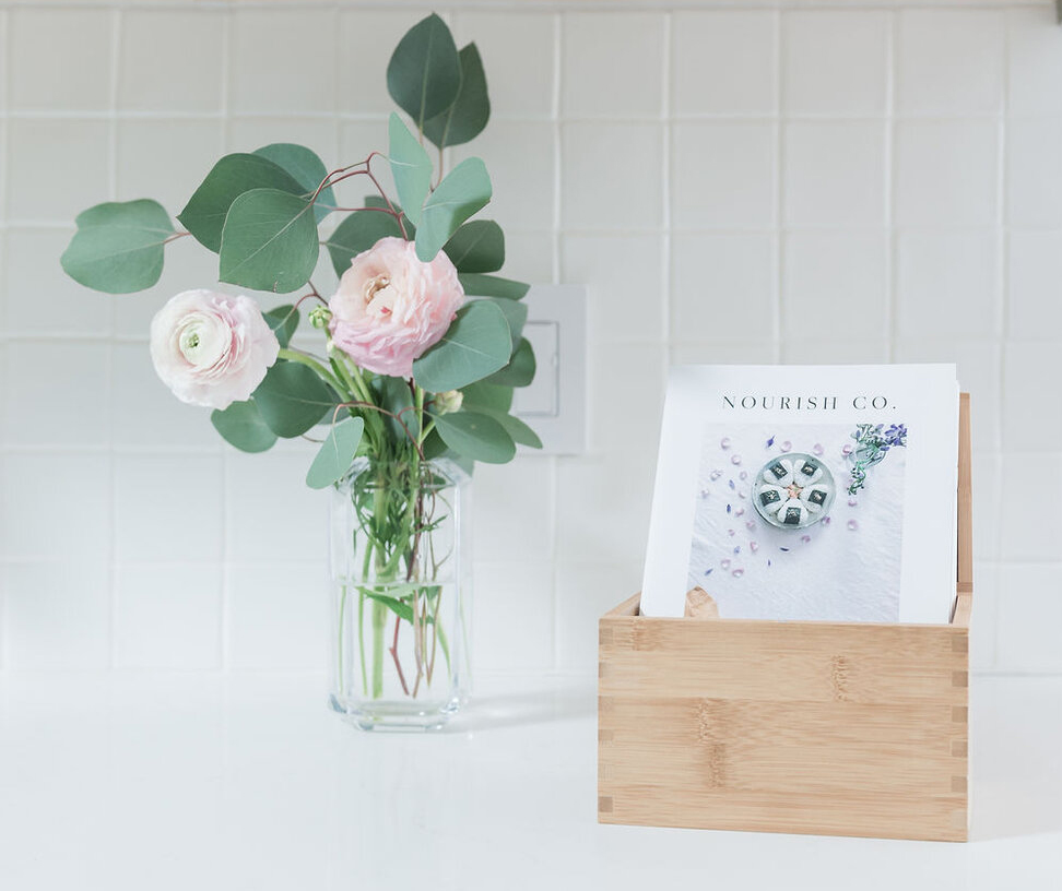 A cooking zine in a wooden box sits to the right of a glass vase of flowers on a white counter.