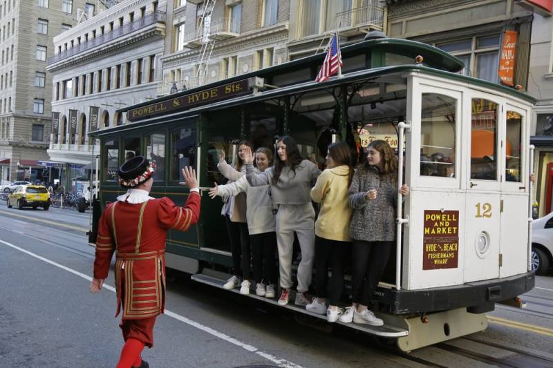 Sweeney greets a group of girls riding a cable car outside the Sir Francis Drake Hotel.