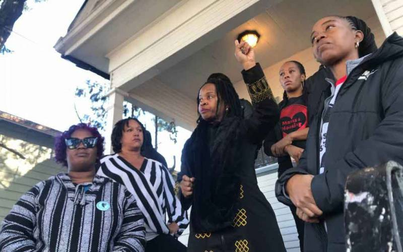 Members of the group Moms 4 Housing — Sharena Thomas, left, Carroll Fife, center, Dominique Walker, second from right, and Tolani KIng, right — outside a formerly vacant house on Magnolia Street in West Oakland, which they've occupied since November, despite an eviction order.