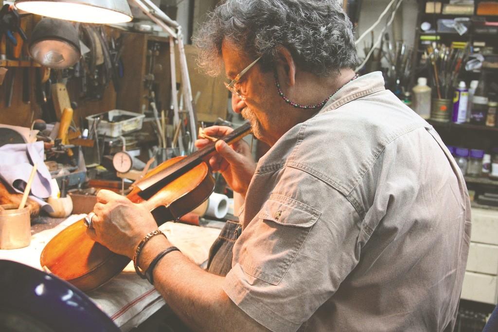 Amnon Weinstein repairing a violin in his Tel Aviv workshop.