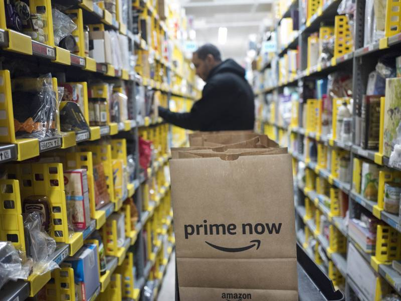 A clerk picks an item for a customer order at the Amazon Prime warehouse in New York.