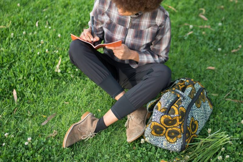 A woman writes in her diary on a lawn.