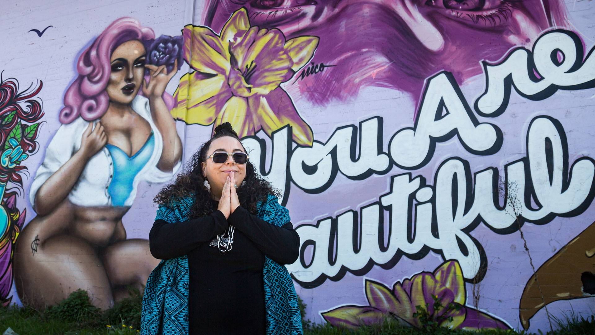 "DJ Agana in front of the 'You Are Beautiful' mural in West Oakland. <a href=""https://www.instagram.com/carla.hr/"" target=""_blank"">Carla Hernandez Ramirez</a>"
