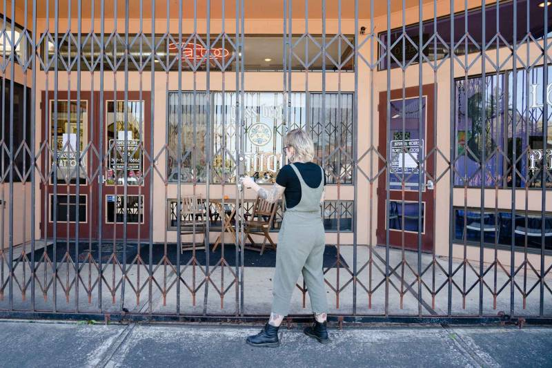 Emma Pierce closes the gates at the tattoo shop.
