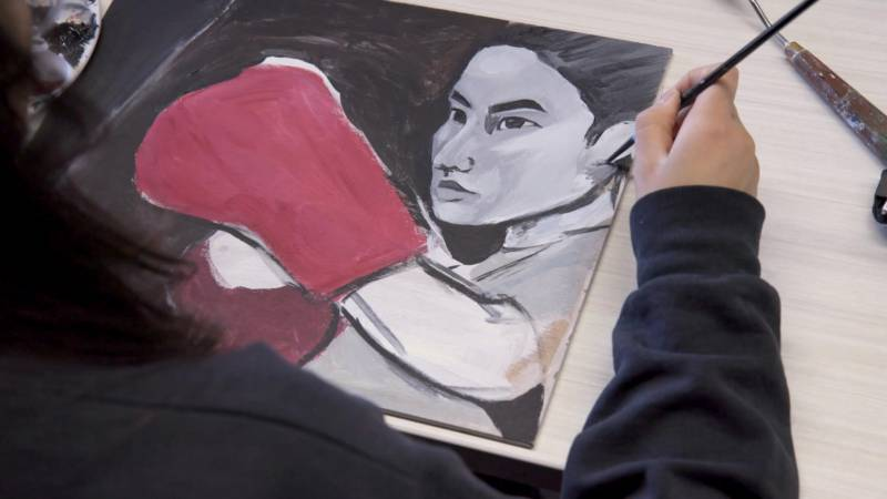 Kathy Liang painting an image of herself boxing