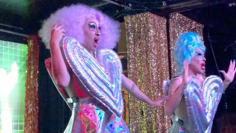 Two drag queens wear inflatable, sparkly costumes an colorful wigs on stage.
