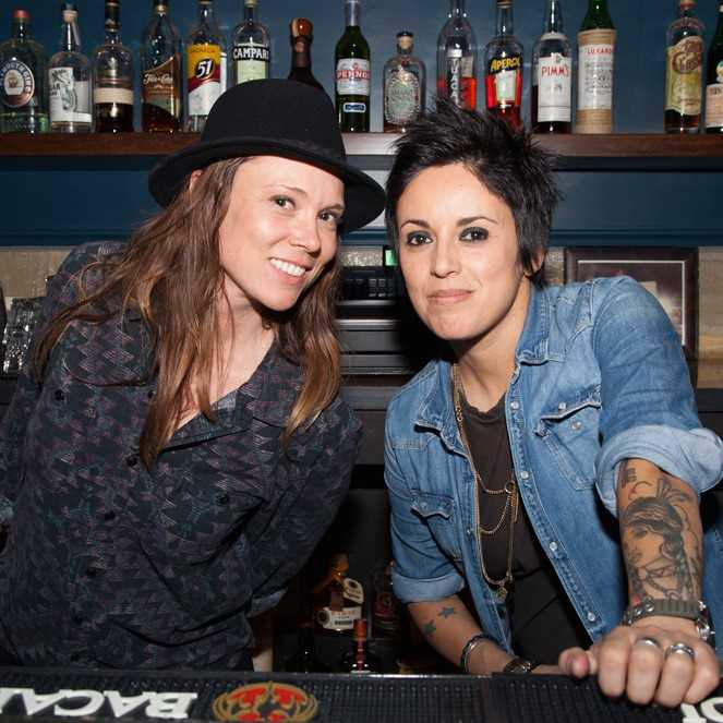 Two women pose in front of a bar.