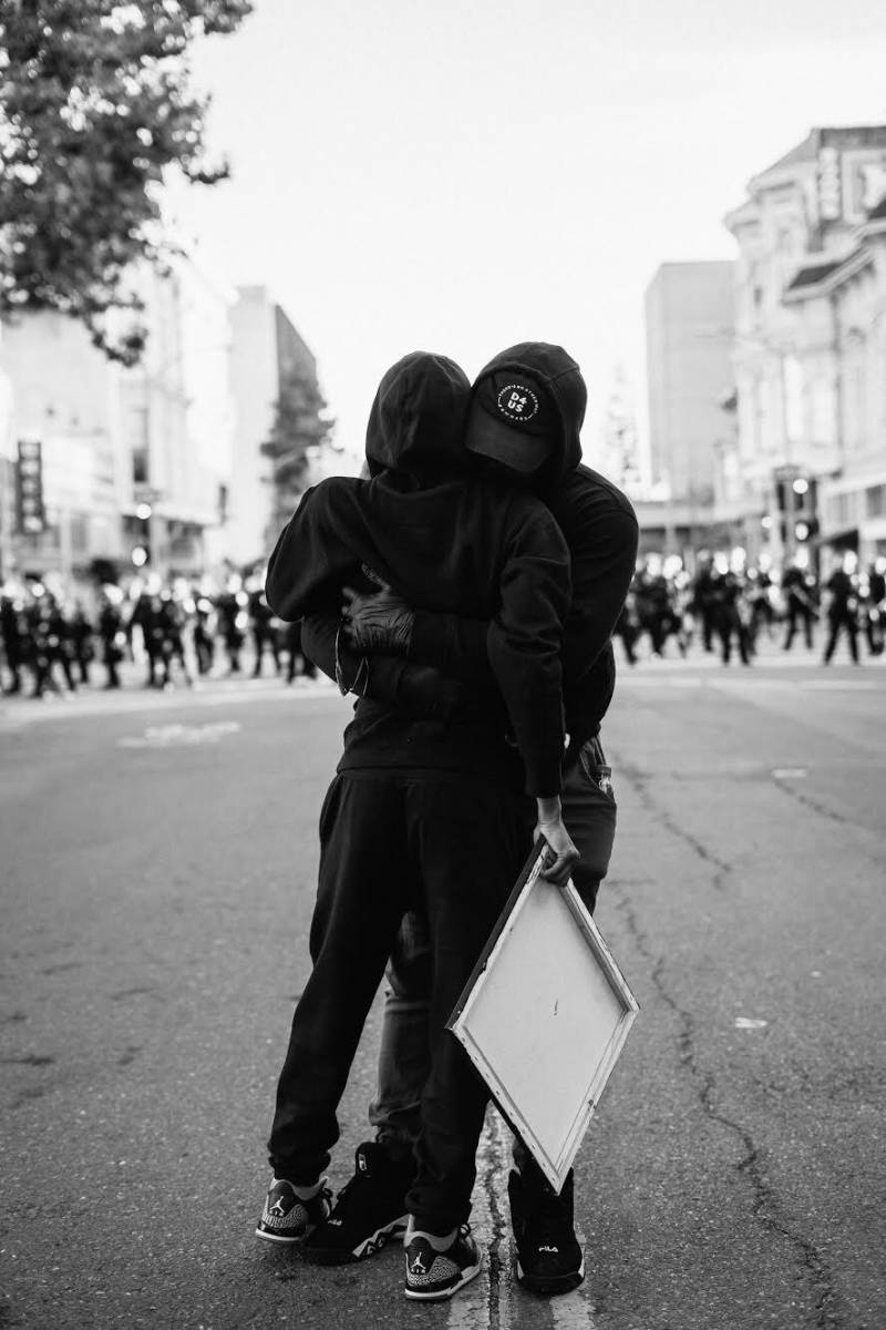Two people wearing all black hug, behind them we see a police line in the distance.