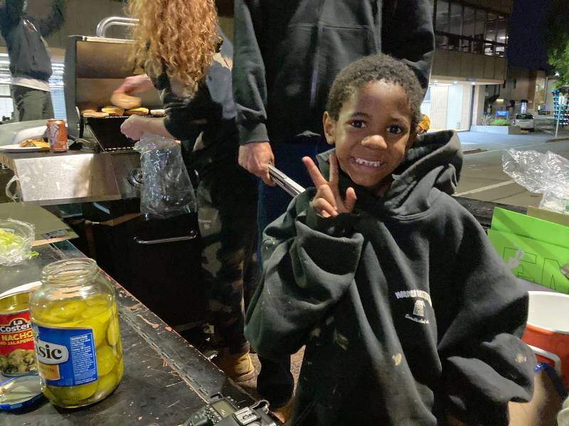 """Kamari Houston, 5, helps serve food in Santa Rosa on Friday, June 5. He's talked his mother Onjelle into coming out each night: """"He seen it on the news and told me 'Mama, I have to go out there, I have to be a part of that.'"""""""