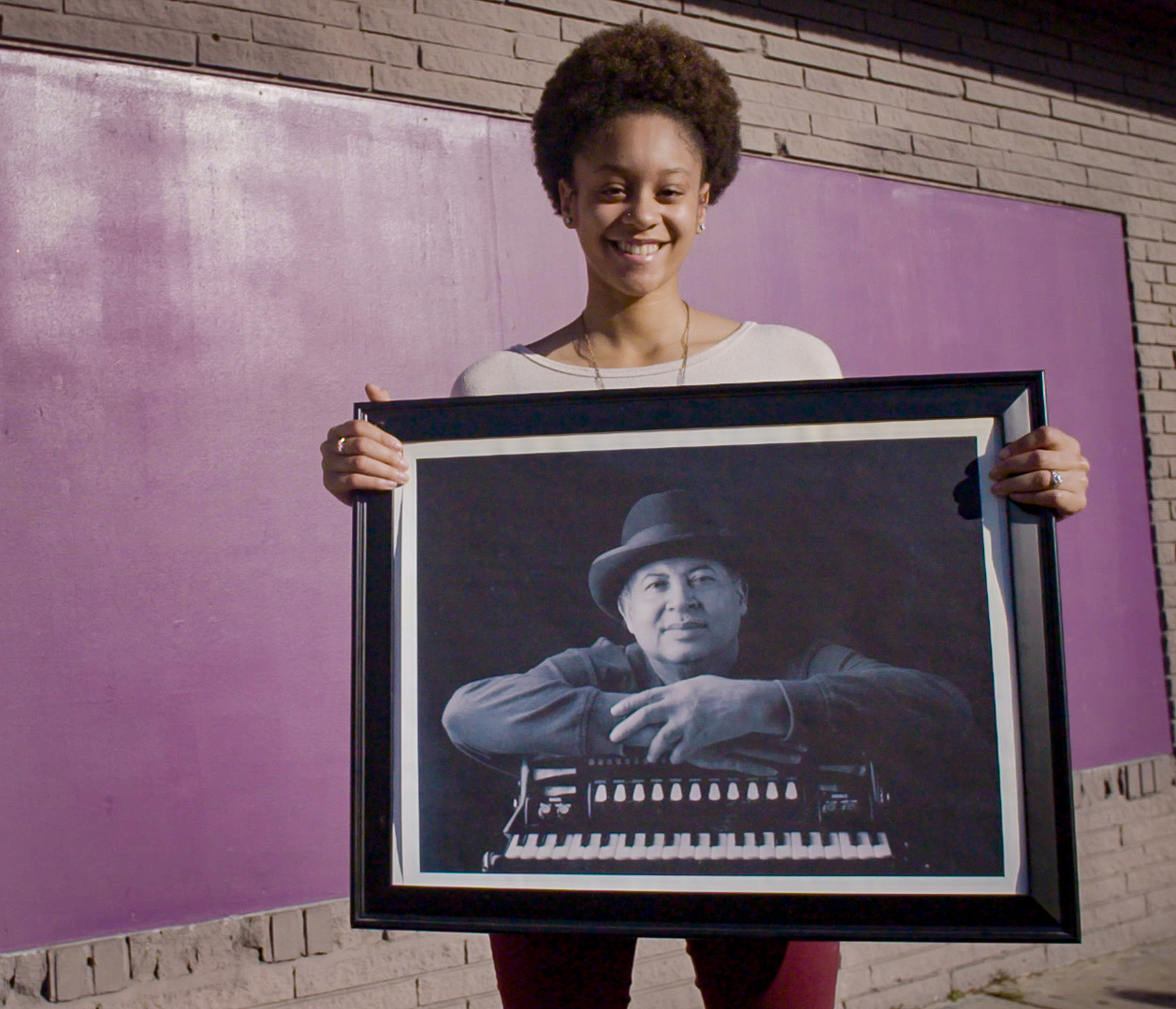 Alexis Jolivette holding up a photograph of her grandfather, zydeco musician Wilfred Chevis. (Photo by MJ Johnson)