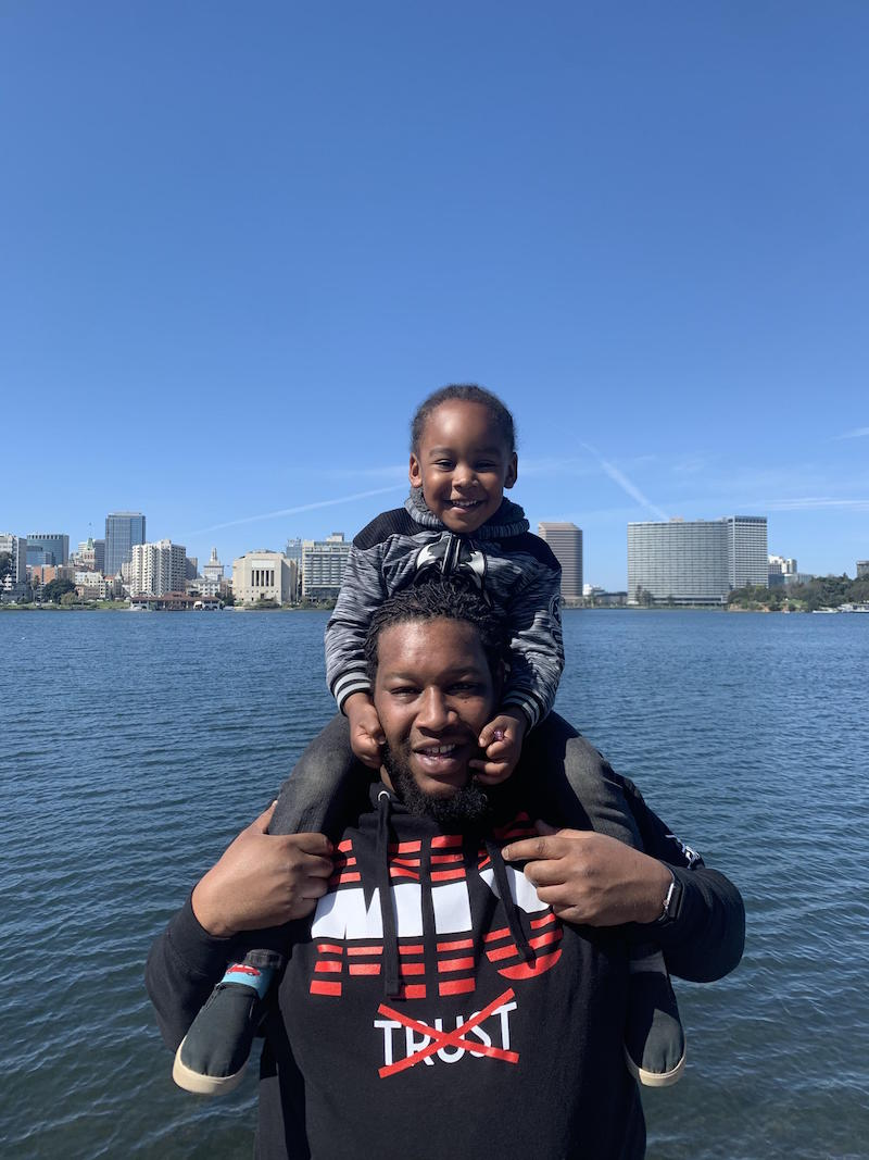 A father and son pose in front of Lake Merritt and the Oakland skyline.