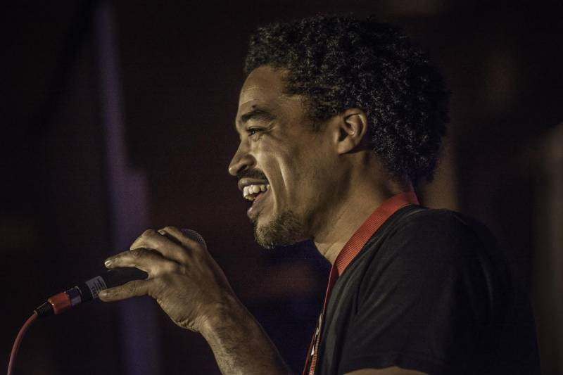 Poet and cheesecake baker Victor Harris Jr. on the mic at an event, shown in profile smiling.