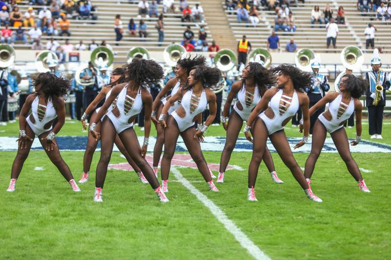The Prancing J-Settes, the majorettes of the Jackson State University, pose in matching silver bodysuits on a football field.