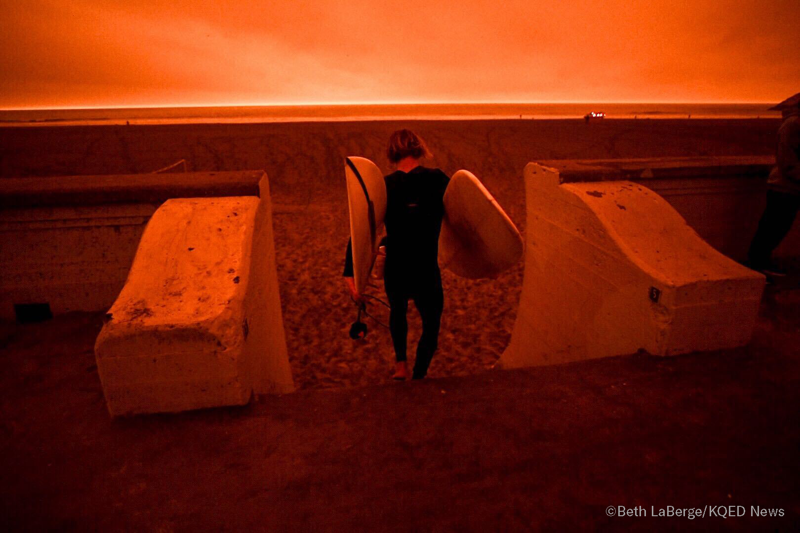 A surfer heads to Ocean Beach in San Francisco under smoke-filled orange skies, on Sept. 9, 2020.