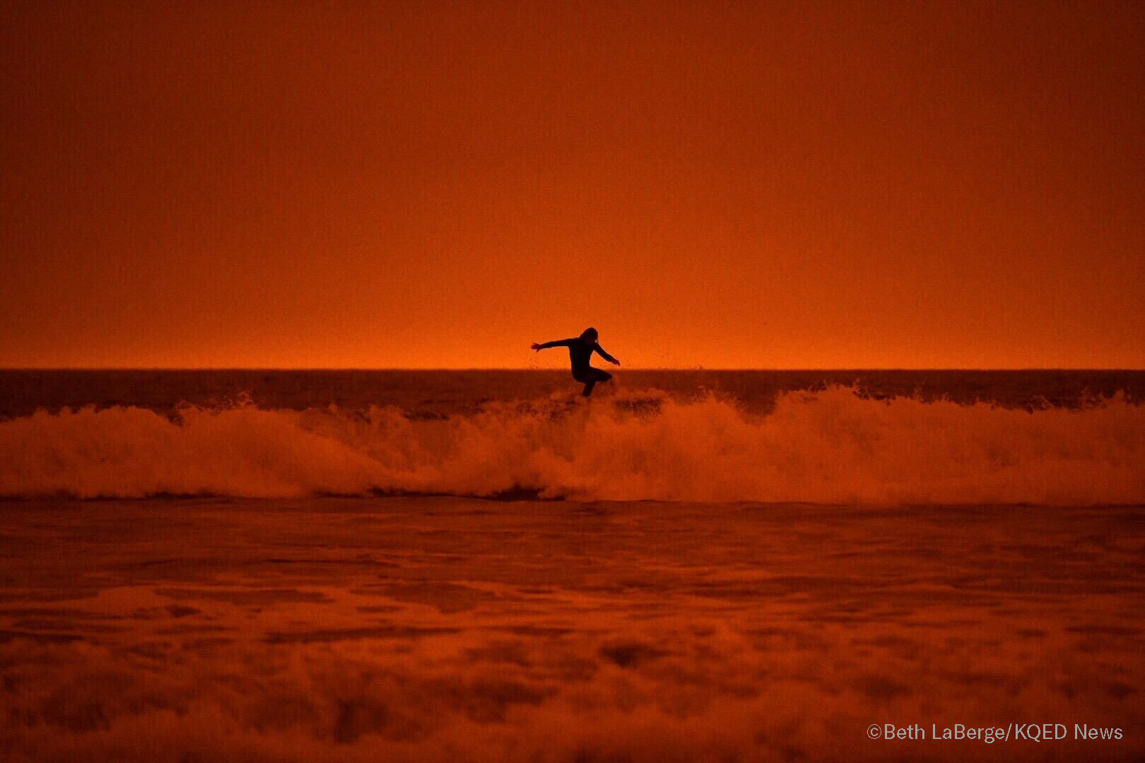 A surfer rides the waves of Ocean Beach in San Francisco under smoke-filled orange skies, on Sept. 9, 2020.