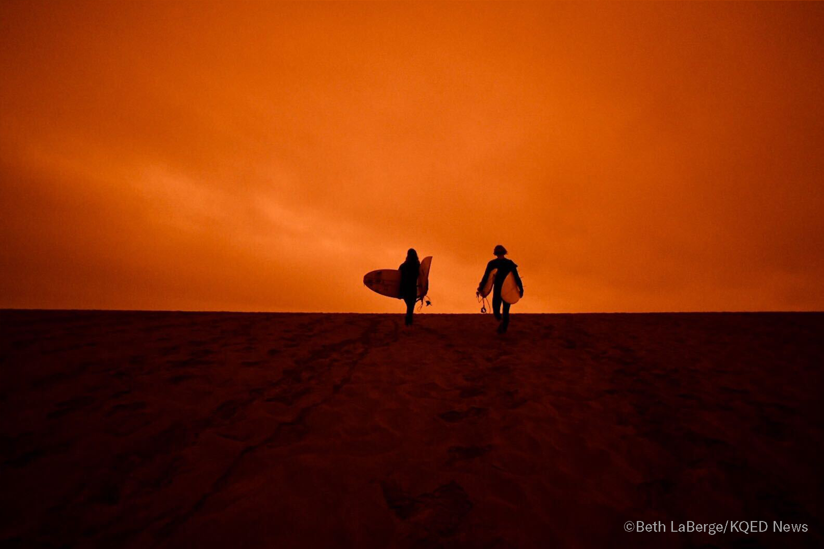 Surfers head for the the waves of Ocean Beach in San Francisco under smoke-filled orange skies, on Sept. 9, 2020.