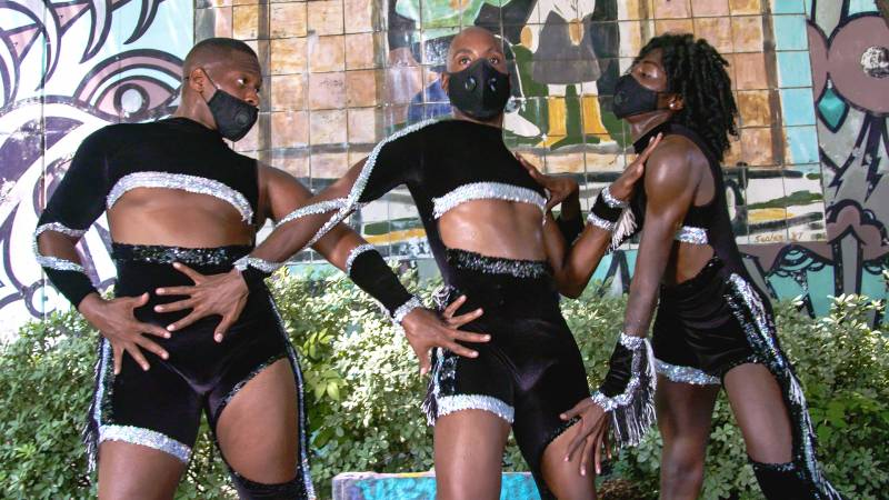 """Three Black dancers who are members of Dance Champz of Atlanta pose in matching black velvet outfits in front a mosaic art piece title """"The Fiddler"""" that sits on a wall behing them."""