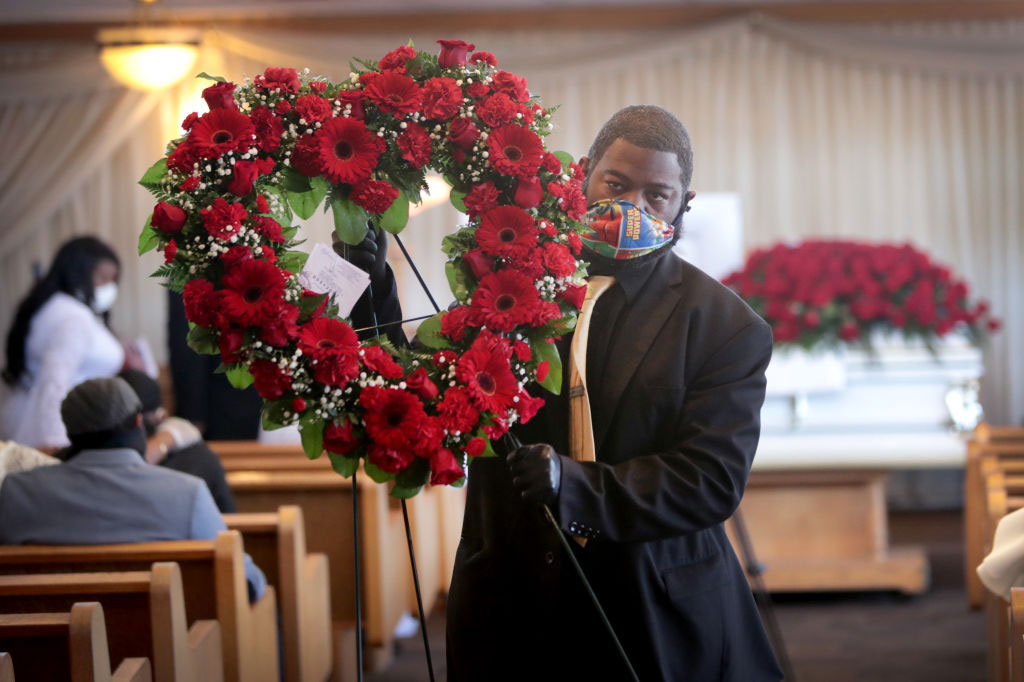 Terrence Bardney of Leak and Sons' Funeral Chapels carries flowers from the chapel following a service on April 16, 2020 in Country Club Hills, Illinois.