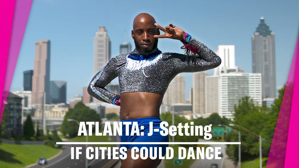 Black male dancer poses in sparkly grey top and bright blue shorts with the Atlanta, GA skyscrapers in the background.