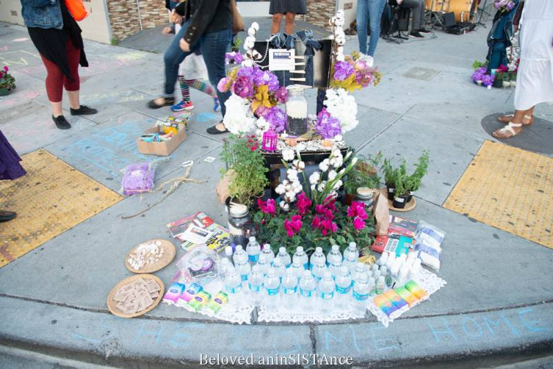A pandemic altar for the Beloved with water bottles, flowers, condoms, and PPE.