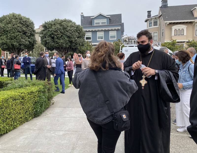 An Armenian Orthodox priest speaks to a group of people informally gathered in a church courtyard.
