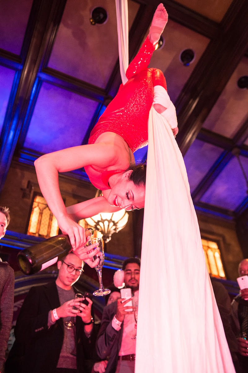 An aerialist hangs from silk while pouring champagne.