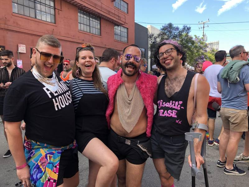 Four smiling friends pose at a Pride celebration.