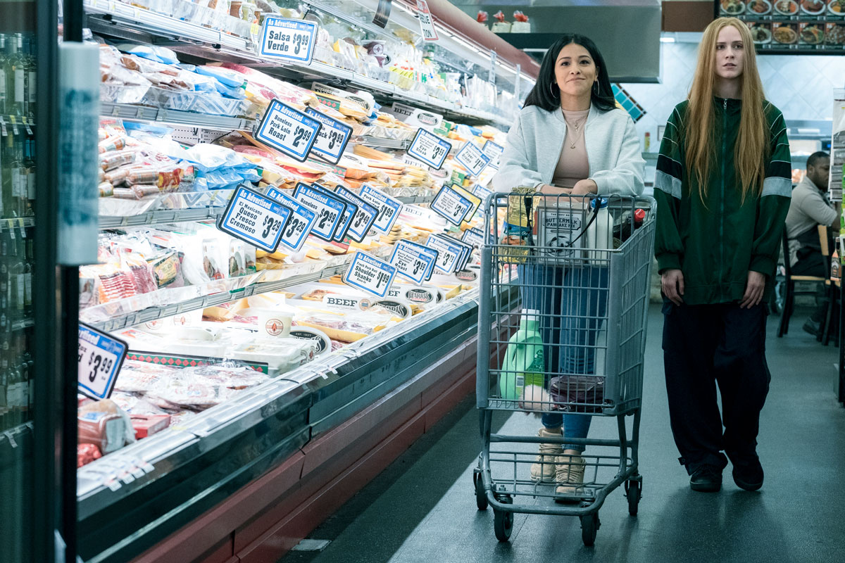 A woman in a white jacket and a woman in baggy clothes push a shopping cart next to a refrigerated display in a market.