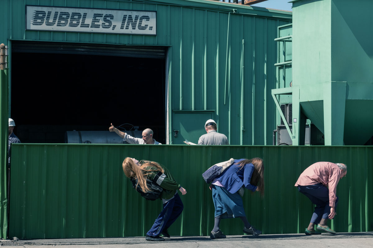 "Three people bend to hide below a low wall outside a green building with a sign that says ""Bubbles, Inc."""