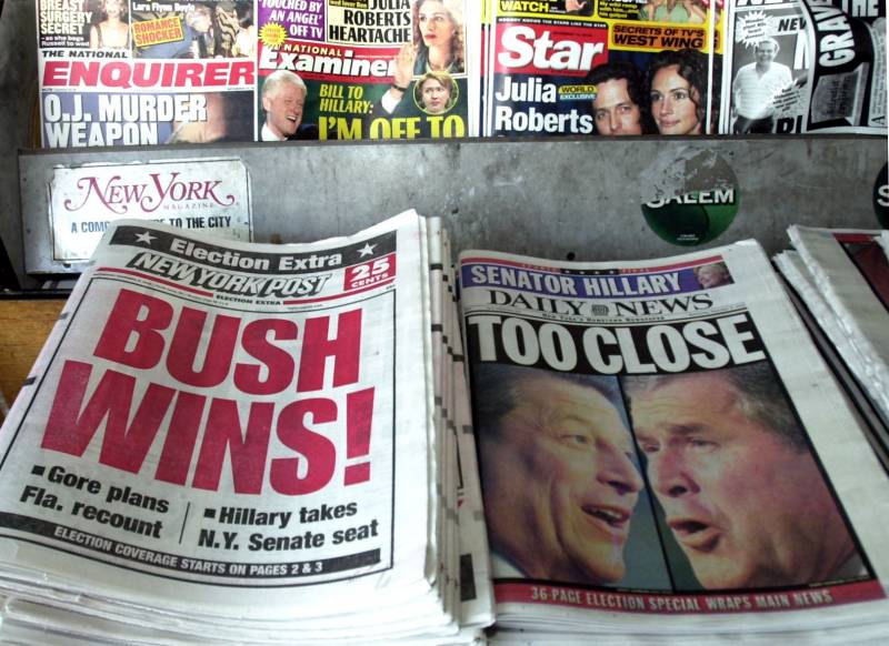 Newspapers sit side by side at a newstand. 'The New York Post' proclaims Texas Gov. George W. Bush the winner of the presidential election, while the 'New York Daily News' says the election is 'Too Close.' November, 2000.