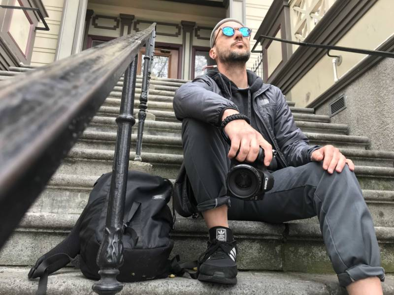 Photographer Scott La Rockwell holding a camera and sitting on a stoop in Oakland.