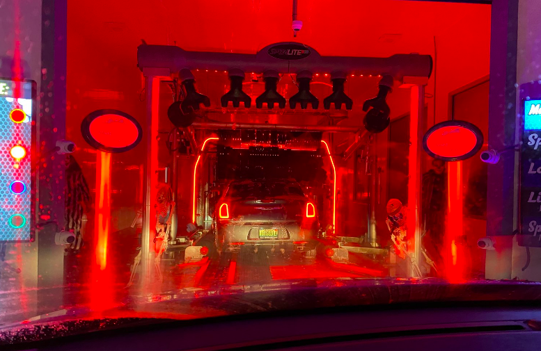 The entrance to a red-lit haunted car wash.