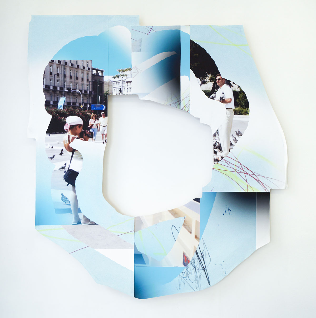 Blue and white mixed media piece with vacation snapshots and a cut-out center, revealing white gallery wall.