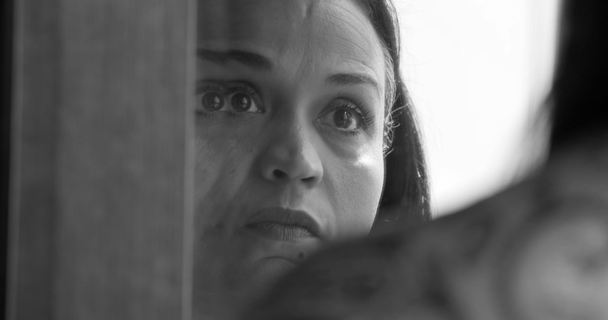 Black-and-white-image of a woman's face seen though a pane of glass over someone else's shoulder, distortion makes her left eye appear doubled.