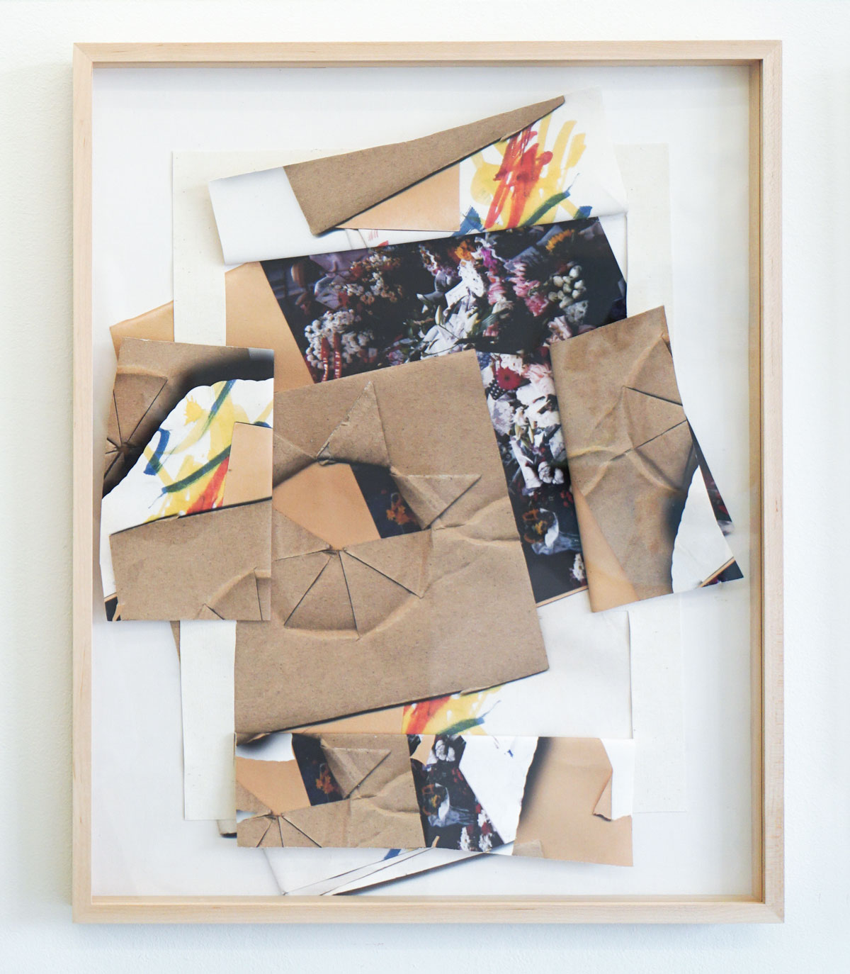 Light wood frame around a mixed media work, collaged images of brown paper cut and folded in a star pattern, childlike marker drawings and a photograph.