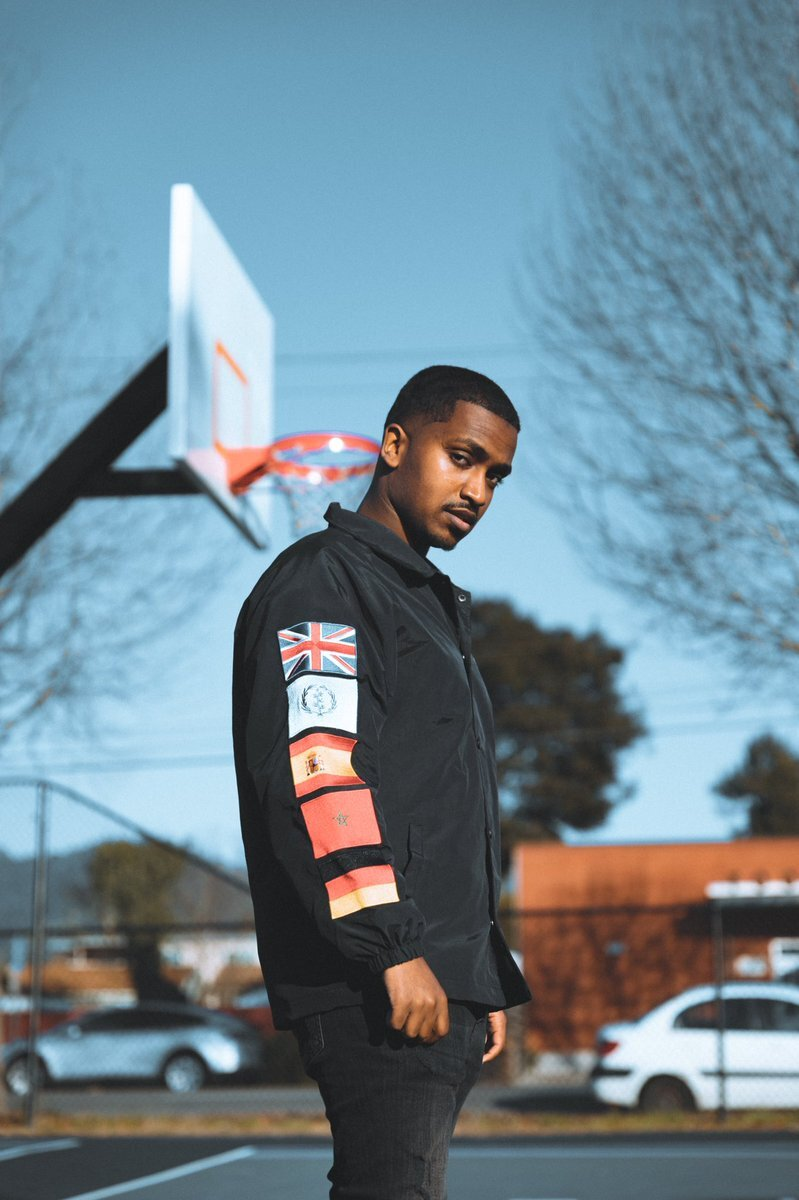 A Black man wearing a black bomber jacket with flags running down the arm stands in front of a basketball hoop. The camera looks up at him, and he looks down at the camera from a sideways glance. The trees are out of focus in the background, the bigger trees have already lost all their leaves and the sky is clear with no clouds.