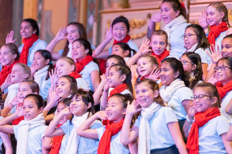 A chorus of young girls raise their hands to their ears while smiling.