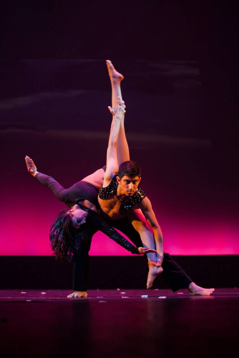 Two young male and female dancers of South Asian heritage are seen performing Bollywood and Indian contemporary dance styles on stage.