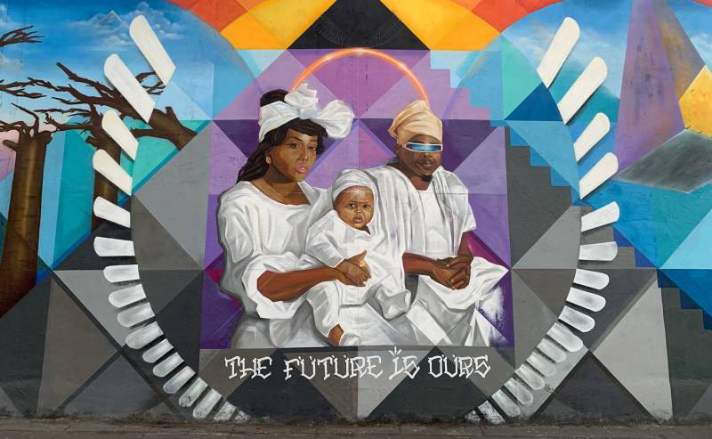 A mural on 14th Street in West Oakland, depicting Jazz Hudson, Olafemi Akintunde and their son Selah.