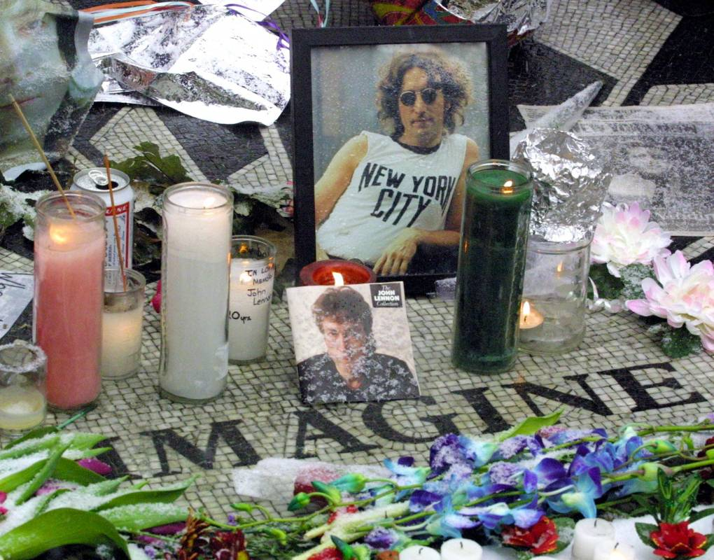 One of Bob Gruen's iconic John Lennon photos is seen amongst flowers and candles at the Central Park memorial to the Beatle, December 2000.