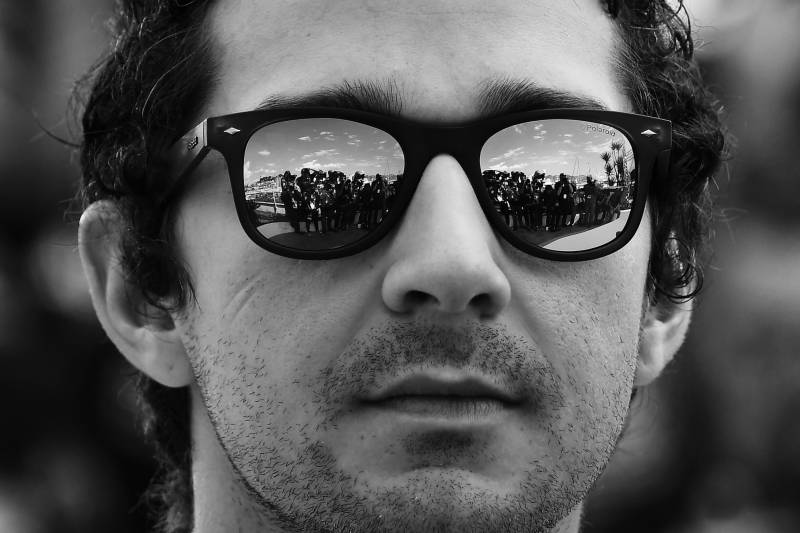 A close-up image of Shia LaBeouf wearing sunglasses at the 69th Cannes Film Festival in 2016.