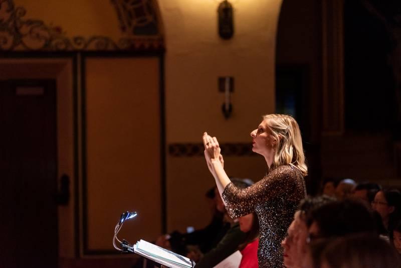 A woman at a podium conducts a chorus.