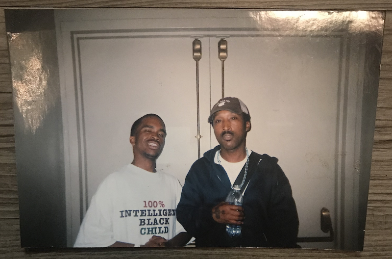 "Pendarvis Harshaw wearing a ""100% Intelligent Black Child"" shirt while standing next to D'Wayne Wiggins backstage at the S.O.S. Hurricane Katrina Benefit Concert in Oakland."
