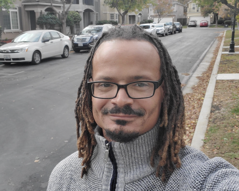 Vincent-Ray Williams III wears a grey sweater and glasses as he poses for a photo on the street.