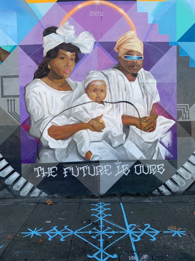A line is shown, drawn though an image of the Black family at the center of the mural on 14th st. in West Oakland