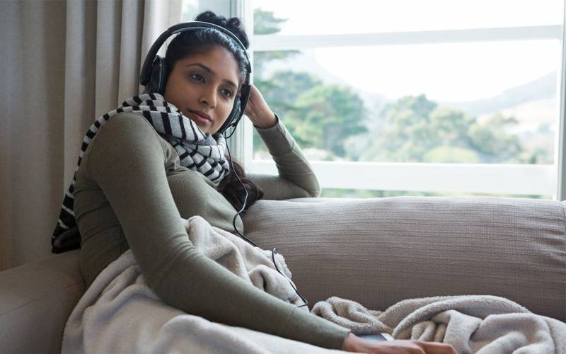 A woman sits on the couch listening to headphones.