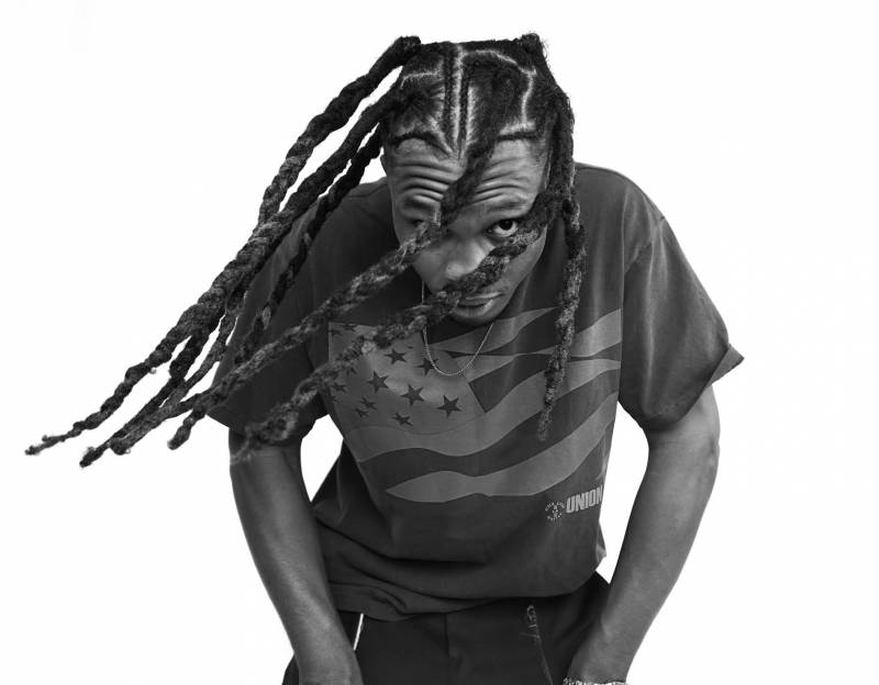 YMTK swinging his locs as he poses for a photo.