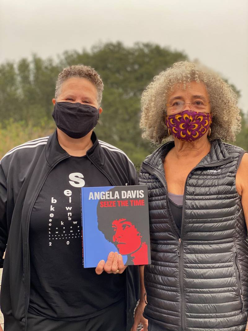 Lisbet Tellefsen and Angela Davis wear masks to protect from COVID-19 as they pose for a photo while holding a copy of the book, 'Seize the Time.'