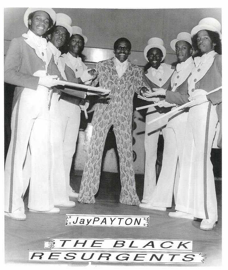 The Black Resurgents form a semi circle around TV host Jay Patton and post for a photo